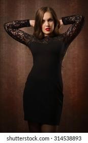 Pretty woman in a black dress in the boudoir