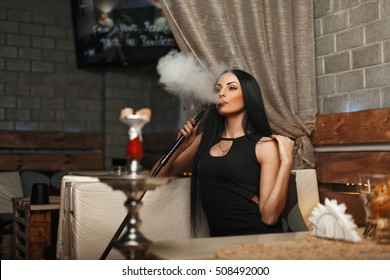 Pretty woman in a black dress resting in a bar and smokes a hookah.