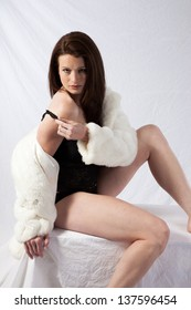 Pretty woman in black lingerie and  a white fur coat, looking at the camera with a friendly, sexy expression