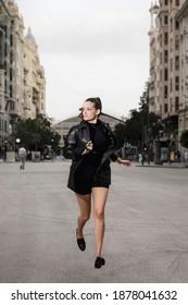 Mujer bonita con pantalones cortos negros y chaqueta negra corriendo por la calle, huyendo de la pandemia, corriendo y haciendo deportes con ropa informal y cola de ponytail. Capturado en el aire