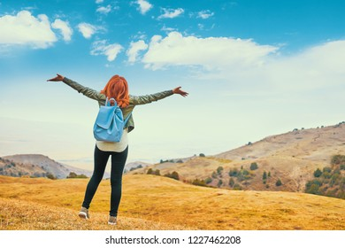 Pretty woman with blue backpack outdoors enjoying nature mountains and arms outspread in celebration of a beautiful sunny summer day and freedom