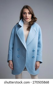 Pretty woman in blue coat posing on grey background