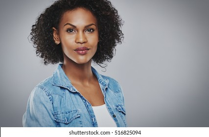 Pretty woman with blue jean shirt and white top on gray background