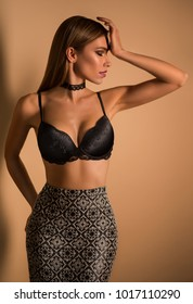 Pretty woman in bra and skirt posing at camera against brown background