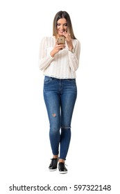 Pretty woman in braided shirt smiling while reading cellphone message. Full body length portrait isolated over white background.