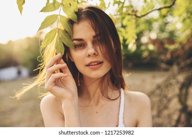 pretty woman with a branch near the face in nature