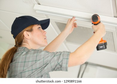 pretty woman with building puncher drilling hole in ceiling