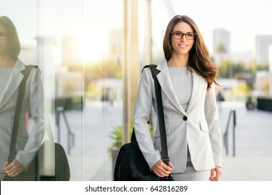 Pretty woman in business suit with bag stylish trendy with glasses and professional executive theme