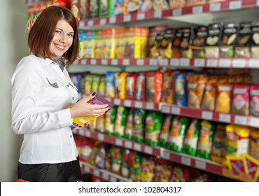 Pretty woman buyer in grocery shop at shelves with products