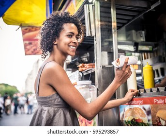 Pretty woman buying a hot dog in a kiosk in New York