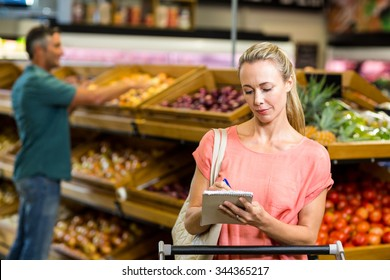 Pretty woman checking grocery list at the supermarket