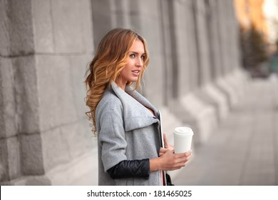A pretty woman with a coffee to go against urban scene.