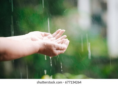 Pretty woman collects rain with her hands