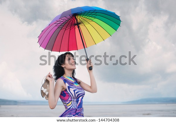Pretty woman with colorful umbrella and with the white sandals in her hand