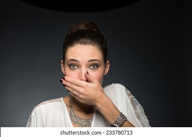 Pretty woman covering mouth with hands. Speak no evil concept.