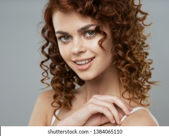 Pretty woman with curly hair makeup cosmetics shampoo gray background