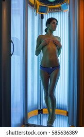 pretty woman or cute girl with sexy naked healthy body standing in solarium spa salon in pants, cover chest with hand