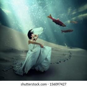 a pretty woman dancing underwater in the ocean