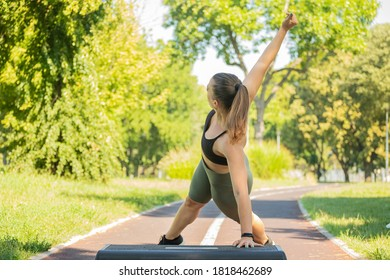 Pretty woman doing exercises on stepper in nature