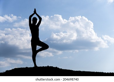 Pretty woman doing yoga exercises in the park. silhouette.