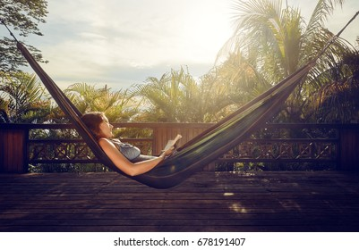 pretty woman in a dress read book in a hammock during a vacation.