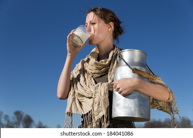 pretty woman is drinking fresh milk in front of blue sky