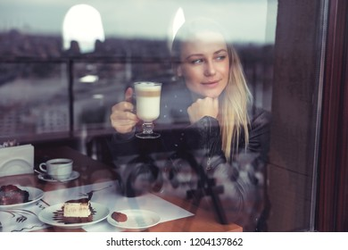 Pretty woman drinking latte in cafe and looking through the window, enjoying warm sweet beverage in cozy place, nice peaceful autumn weekend