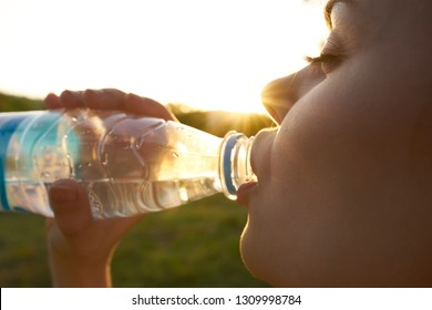 Pretty woman drinking water from a bottle on the nature