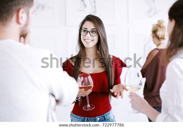 Pretty woman drinking wine during meeting with friends. Art gallery concept