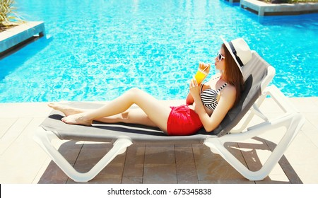 Pretty woman drinks juice from cup at summer on a deckchair over a blue water pool background
