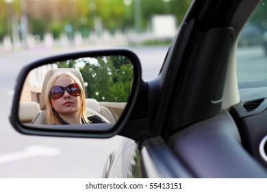 Pretty Woman Driving Her Convertible Sports Car With Her Sunglasses