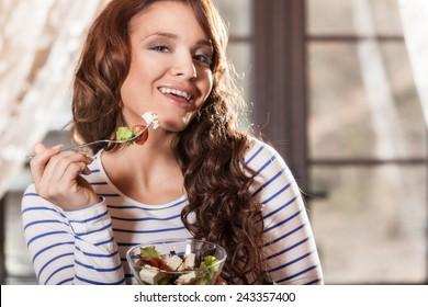 Pretty woman eating fresh vegetable salad