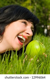 pretty woman eating green apple on the summer glade