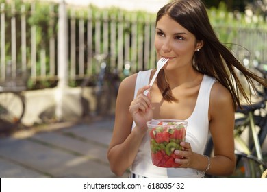 Pretty woman eating a healthy fresh fruit salad from a plastic tub licking the fork with appreciation as she stands outdoors