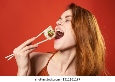 Pretty woman eats rolls with chopsticks sushi red background fastfood