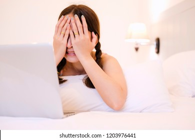 pretty woman in emotional serious by reading news a social network in laptop on bed