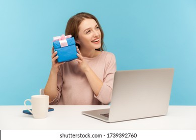 Pretty woman employee sitting at workplace and holding gift near ear, listening with interest what's inside box, curious about birthday surprise, bonus for good job. indoor studio shot, isolated - Shutterstock ID 1739392760
