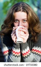 Pretty woman enjoying a cup of coffee outdoors