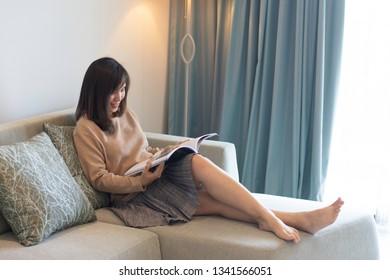 Pretty woman enjoying reading a book on her living room sofa.