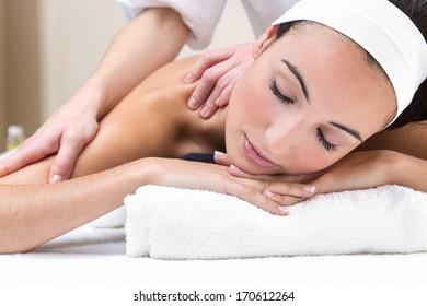 Pretty Woman enjoying shoulder massage at beauty spa