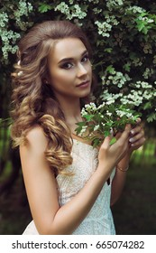 Pretty woman enjoying smell flowers. Portrait of young beautiful woman posing among blooming trees