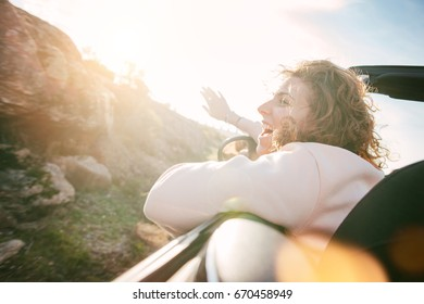 Pretty woman enjoying the sunset and having fun in a convertible