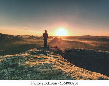 Pretty woman  enjoys the view of sunset over an autumn forest in deep velly bellow. Enjoy moment ot of people