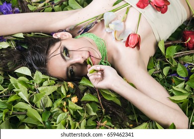 pretty woman with fashionable makeup in green beads with tulip flowers laying on green leaves in spring or summer on natural background