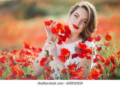 Pretty woman in field of red poppy flowers, spring time