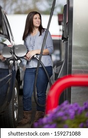 Pretty woman filling her car with petrol at gas statiion