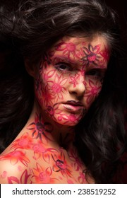 Pretty woman with flowers face art. Red flowers on face. Brunette hair. Face art and body art.