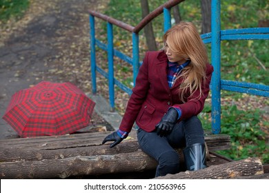 Pretty woman with flowing hair in tweed jacket and leather gloves sits on the old bridge in autumn forest