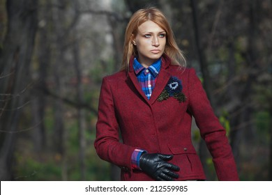 Pretty woman with flowing hair in tweed jacket and leather gloves walking in autumn forest