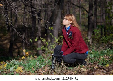 Pretty woman with flowing hair in tweed jacket and leather gloves sitting at grass in autumn forest